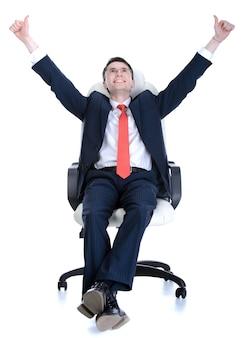 Uomo d'affari bello sicuro che si siede sulla sedia.