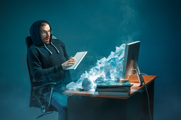 Uomo d'affari bello sollecitato giovani che lavora allo scrittorio in ufficio moderno che grida allo schermo del computer portatile e che è arrabbiato per lo spam