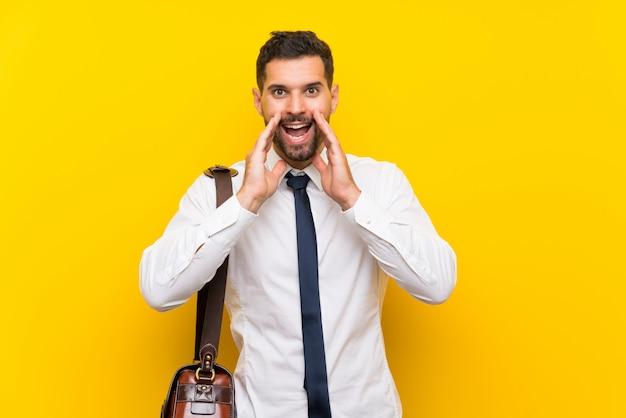 Uomo d'affari bello sopra gridare giallo isolato con la bocca spalancata
