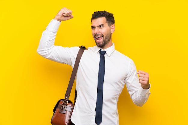 Uomo d'affari bello sopra la parete gialla isolata che celebra una vittoria