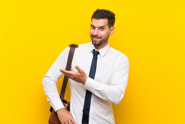 Uomo d'affari bello sopra la parete gialla isolata che estende le mani al lato per l'invito a venire