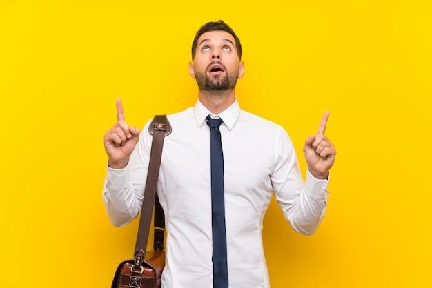 Uomo d'affari bello sopra la parete gialla isolata che indica con il dito indice una grande idea