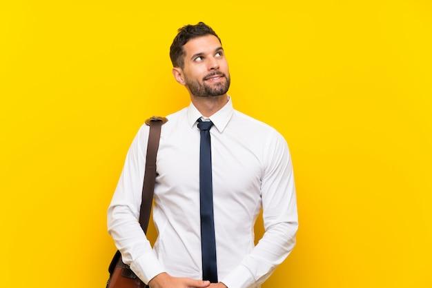 Uomo d'affari bello sopra la parete gialla isolata che ride e che osserva in su