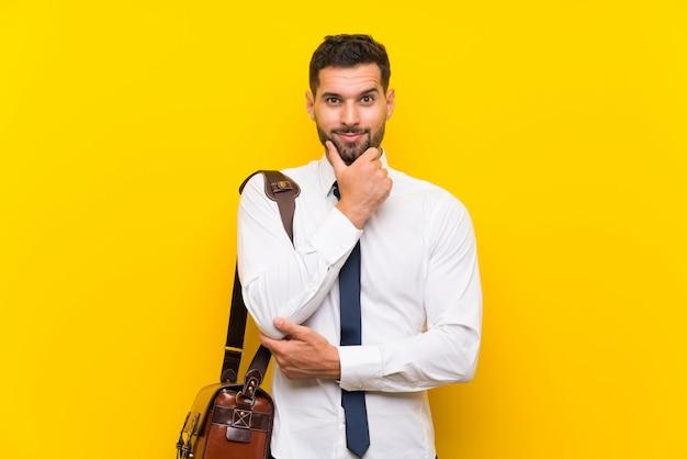 Uomo d'affari bello sopra la risata gialla isolata della parete