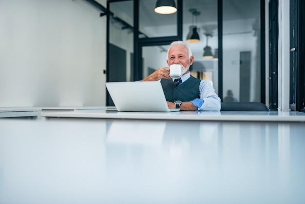 Uomo d'affari bere caffè al lavoro. copia spazio