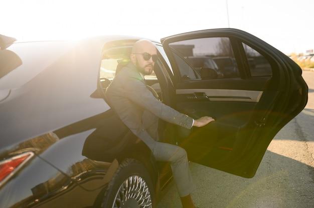 Uomo d'affari calvo con la barba in un vestito costoso in un'auto costosa