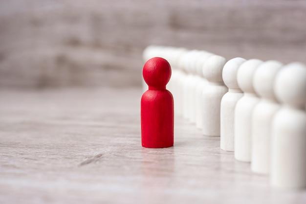 Uomo d'affari capo rosso con folla di uomini in legno. leadership, business, team, lavoro di squadra e concetto di gestione delle risorse umane