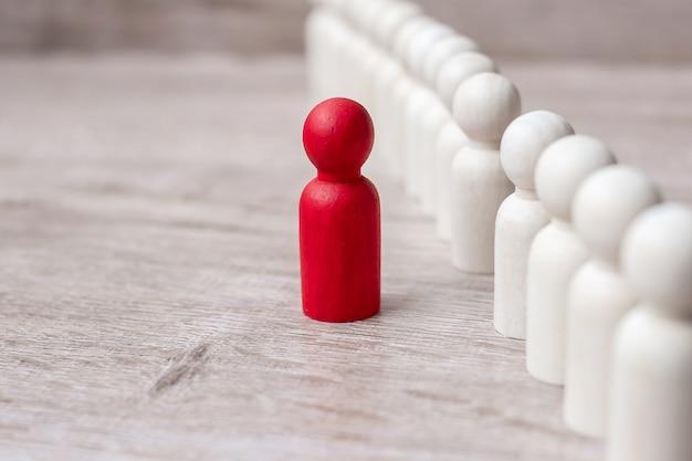 Uomo d'affari capo rosso con folla di uomini in legno. leadership, business, team, lavoro di squadra e gestione delle risorse umane