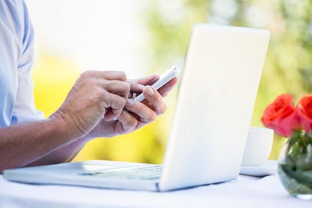 Uomo d'affari casuale che per mezzo del computer portatile e dello smartphone