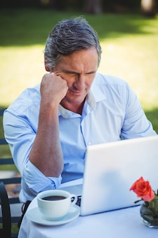 Uomo d'affari casuale che per mezzo del computer portatile e mangiando caffè