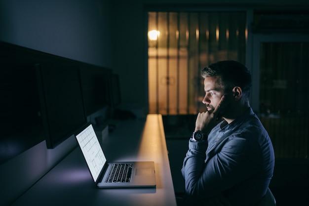 Uomo d'affari caucasico barbuto interessato dei giovani che esamina computer portatile e che trova una soluzione al problema mentre sedendosi a tarda notte nell'ufficio
