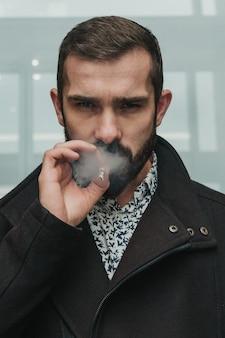 Uomo d'affari caucasico bello con sguardo concentrato che fuma una sigaretta all'aperto.