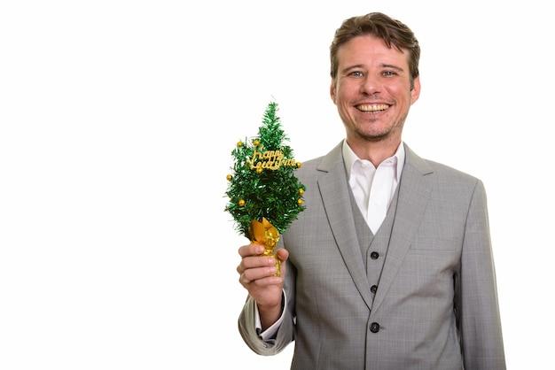 Uomo d'affari caucasico felice che tiene albero di nuovo anno felice