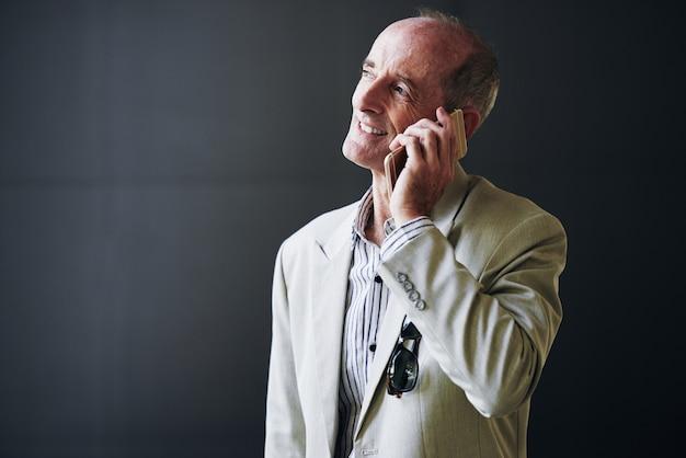 Uomo d'affari caucasico maturo che posa nello studio e che parla sul telefono cellulare