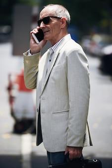 Uomo d'affari caucasico senior in occhiali da sole che stanno in via e che parlano sul telefono