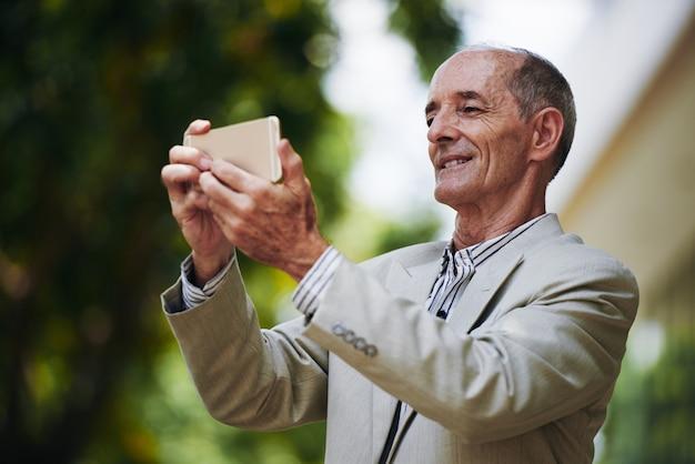 Uomo d'affari caucasico senior nel selfie del takin del vestito con lo smartphone all'aperto