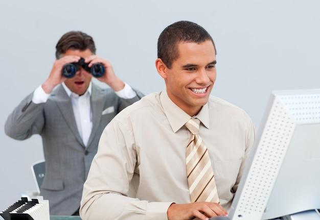 Uomo d'affari charimastic che guarda il computer del suo collega tramite il binocolo