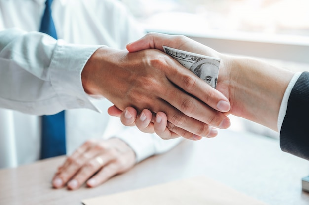 Uomo d'affari che agita le mani che danno le banconote in dollari al direttore aziendale per trattare contratto