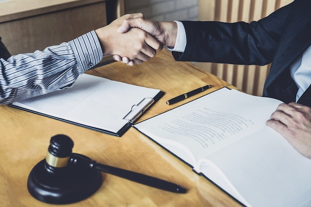Uomo d'affari che agita le mani con avvocato maschio professionista dopo aver discusso buona offerta di contratto