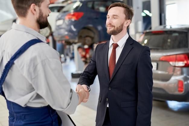 Uomo d'affari che agita le mani con il meccanico