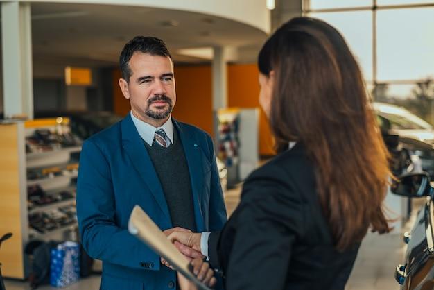 Uomo d'affari che agita le mani con il rivenditore di auto donna.
