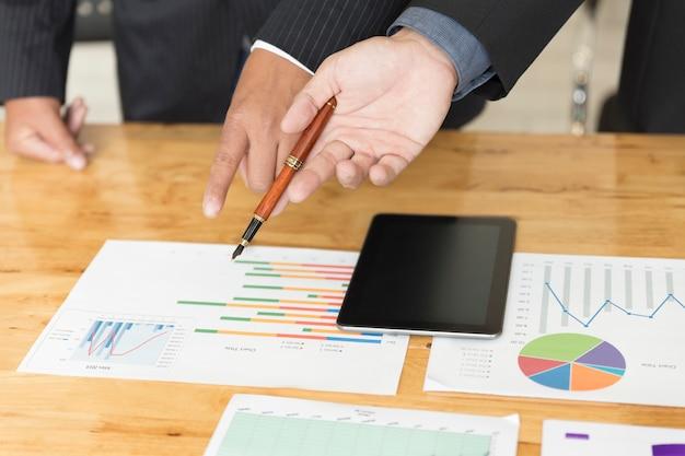 Uomo d'affari che analizza e che discute con il documento del lavoro di ufficio e della compressa