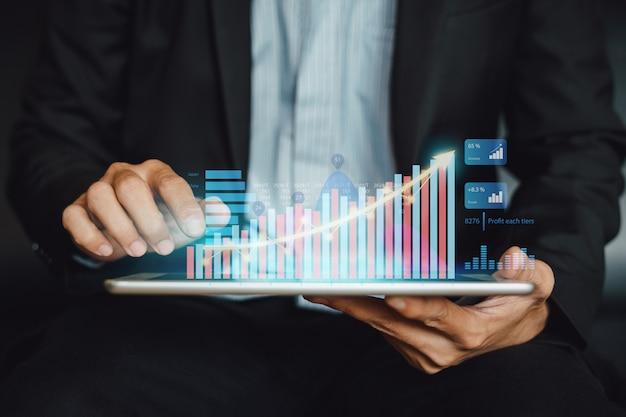 Uomo d'affari che analizza fondo di investimento finanziario con tecnologia grafica digitale di realtà aumentata.