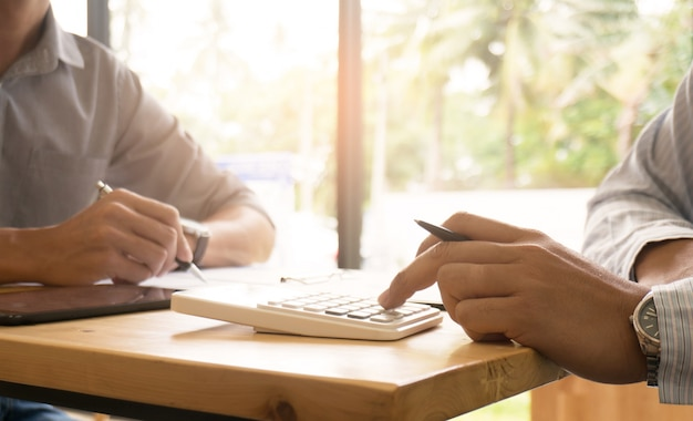 Uomo d'affari che analizza i grafici degli investimenti e premendo i tasti del calcolatore sopra i documenti. concetto di contabilità