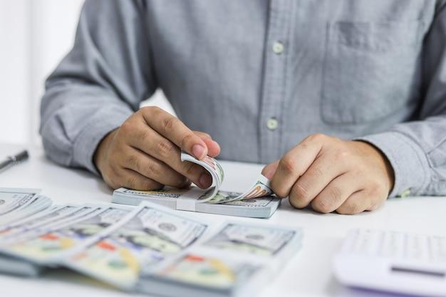 Uomo d'affari che analizza i grafici di investimento e che preme i bottoni del calcolatore sopra i documenti.
