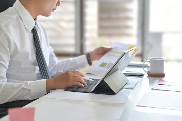 Uomo d'affari che analizza le statistiche finanziarie visualizzate sullo schermo della compressa.