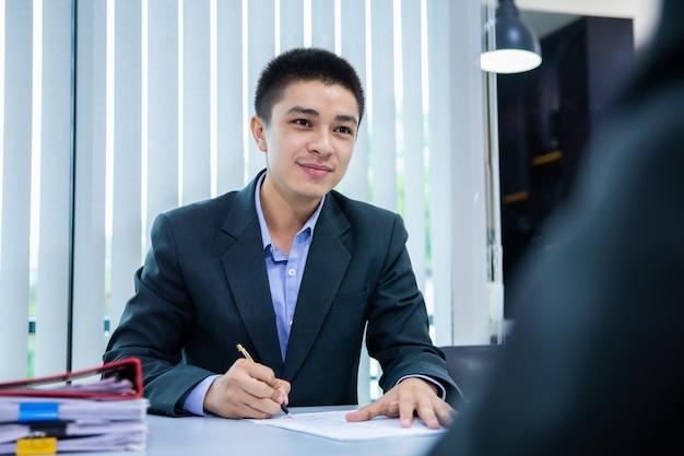 Uomo d'affari che ascolta le risposte del candidato che spiegano sul suo profilo, concetto di colloquio di lavoro