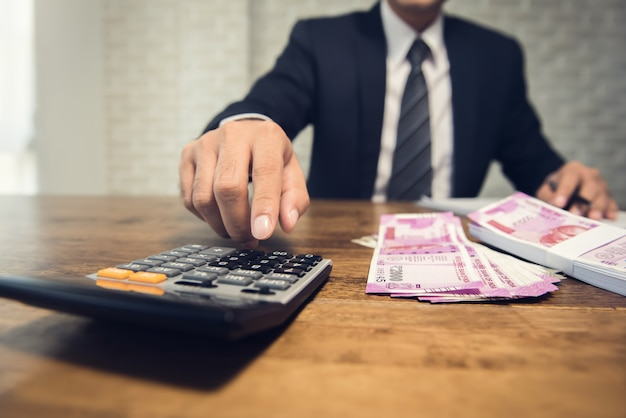 Uomo d'affari che calcola il tasso di conversione per i soldi della rupia indiana