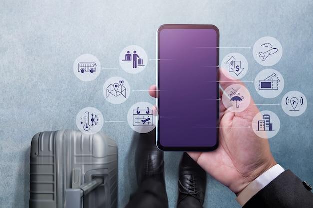 Uomo d'affari che cammina con la valigia e l'utilizzo di tablet per la gestione dei viaggi