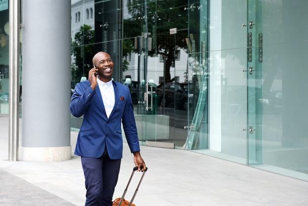 Uomo d'affari che cammina con una valigia e parla al telefono
