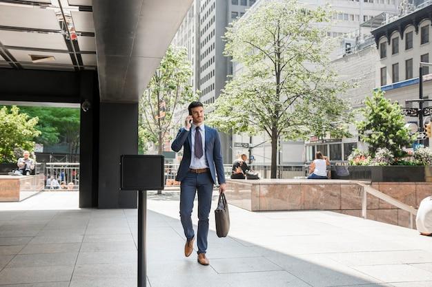 Uomo d'affari che cammina per lavorare e parlare al telefono