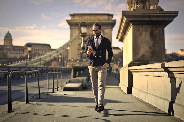 Uomo d'affari che cammina su un ponte
