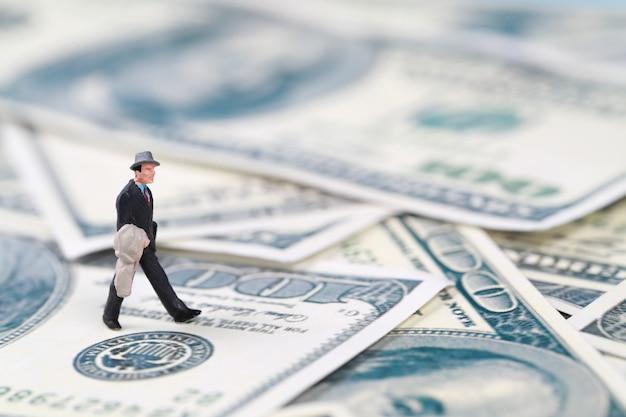 Uomo d'affari che cammina sulle banconote