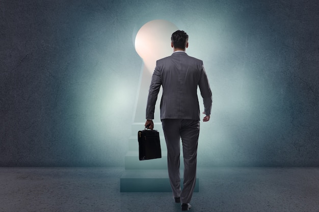 Uomo d'affari che cammina verso la luce dal buco della serratura