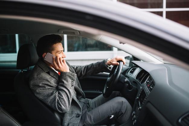 Uomo d'affari che chiama all'interno di una macchina