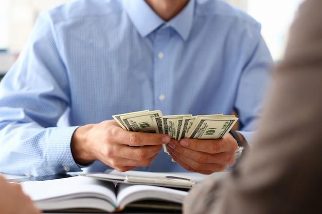 Uomo d'affari che conta i dollari nell'ufficio