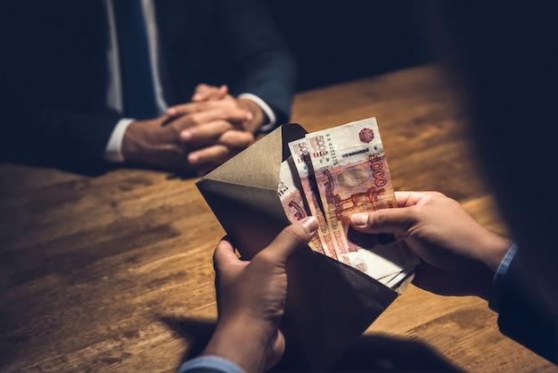 Uomo d'affari che conta rublo russa nella busta marrone dei soldi