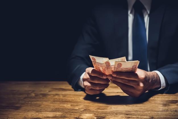 Uomo d'affari che conta soldi, valuta della rublo russa, nella stanza privata scura