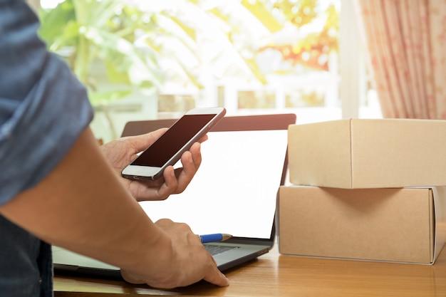Uomo d'affari che controlla iventory sul telefono cellulare con pacco e laptop sul tavolo.