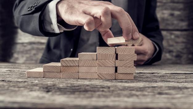 Uomo d'affari che costruisce un grafico o una scala di successo