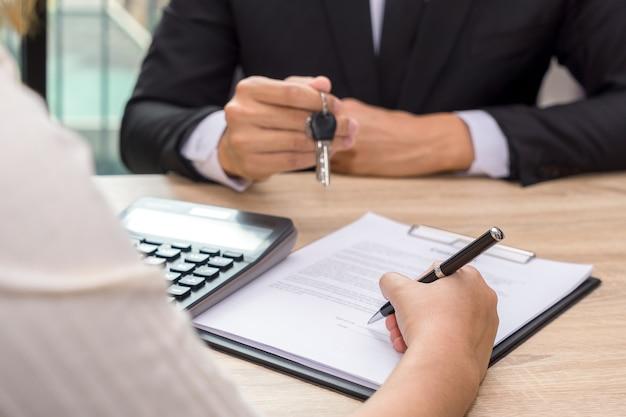 Uomo d'affari che dà le chiavi della casa e contratto di prestito di firma del cliente