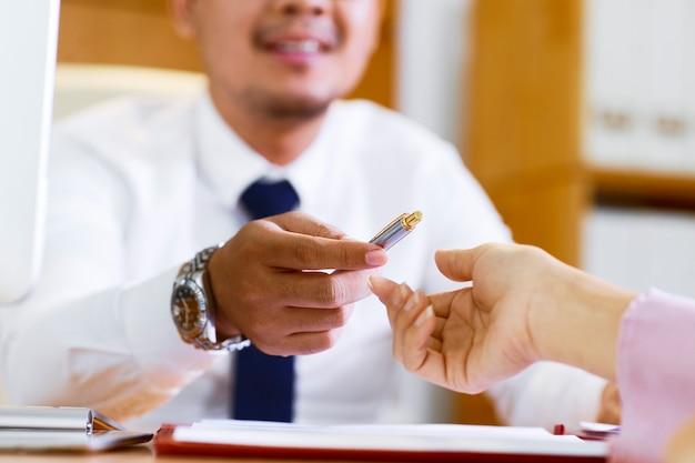 Uomo d'affari che dà penna al cliente