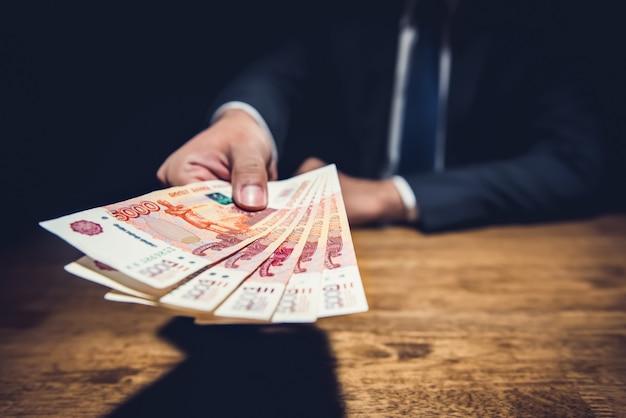 Uomo d'affari che dà soldi, banconote della rublo russa, in un ufficio scuro