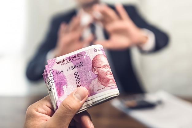 Uomo d'affari che dà soldi sotto forma di rupie indiane come bustarella