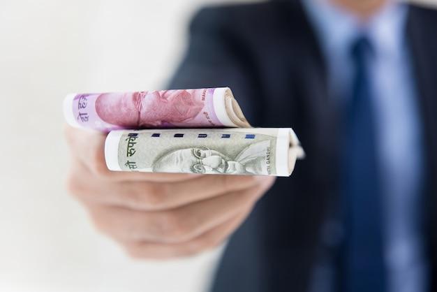 Uomo d'affari che dà soldi sotto forma di rupie indiane f