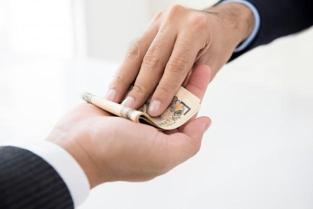 Uomo d'affari che dà soldi, valuta di yen giapponesi, al suo partner in mano
